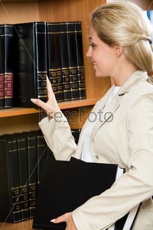 Фотография на тему Фото девушки в профиль, которая достает книгу с полки