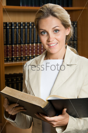 Стильная молодая женщина стоит на фоне полок с раскрытой книгой и улыбается