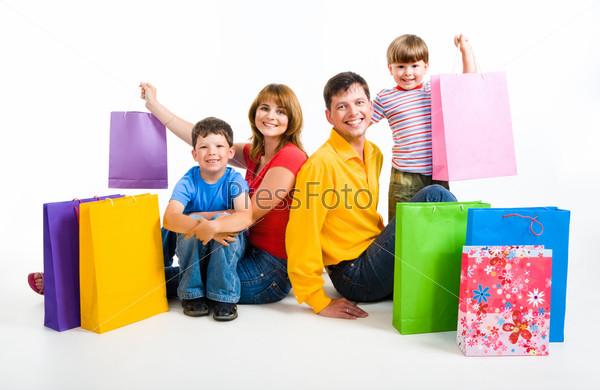 Счастливая семья сидит на полу в окружении разноцветных пакетов с покупками