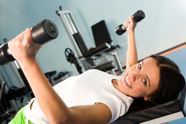 Девушка лежит на тренажере и выполняет упражнения с гантелями глядя с улыбкой в камеру