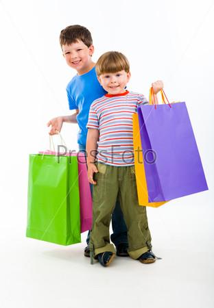 Два веселых мальчика стоят с яркими пакетами и улыбаются