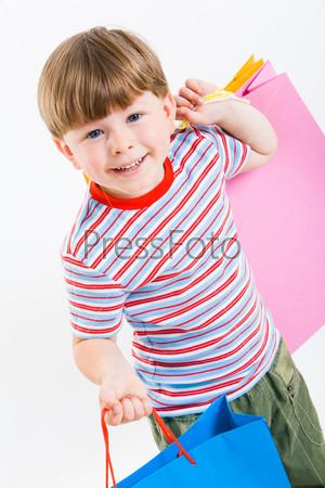 Фотография на тему Крупный план счастливого малыша, который держит в руках яркие покупки