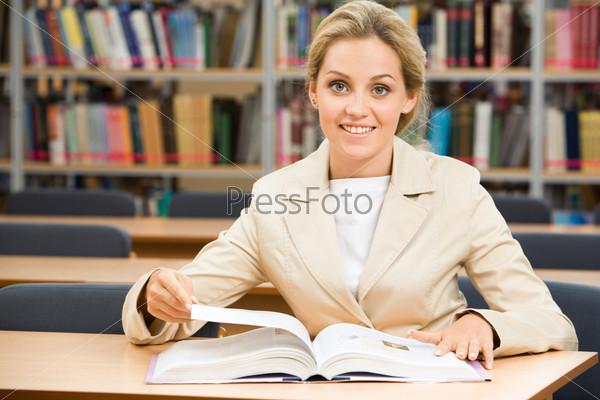 Доброжелательная девушка сидит на фоне полок в библиотеке и мило улыбается глядя в камеру, перед ней раскрытая книга