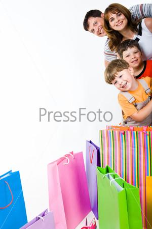 Семья из четырех человек выглядывает из-за угла с задорными улыбками, на полу лежать яркие пакеты с покупками