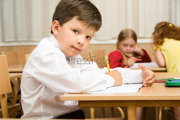Прилежный школьник выполняет в тетради за партой задание учительницы в классе