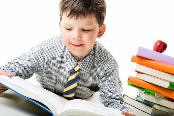 Фотография на тему Мальчик лежа читает раскрытую книгу на фоне стопки ярких книг