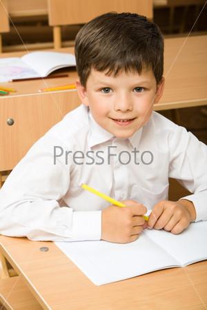 Прилежный ученик сидит за партой в классе перед раскрытой тетрадью с карандашом в руке