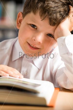 Фотография на тему Озадаченный школьник сидит с раскрытой книгой за столом и подпирает голову рукой