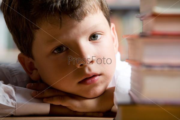 Крупный план школьника лежащего на парте рядом с кипой учебников