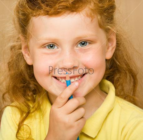 Улыбающаяся ражая девочка с карандашом у рта