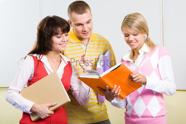 Группа студентов в аудитории смотрит в учебник в руках одной из девушек