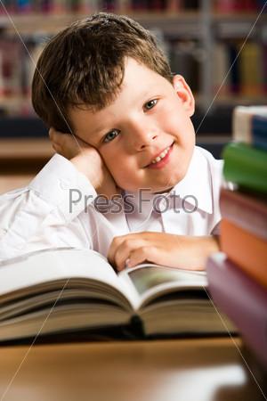 Улыбающийся ученик сидит за столом перед раскрытой книгой, рядом стопка учебников