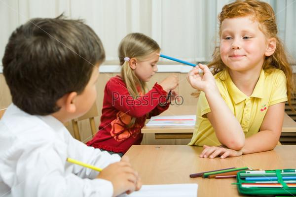 Рыжая девочка объясняет своему однокласснику решение задачи держа в руках карандаш