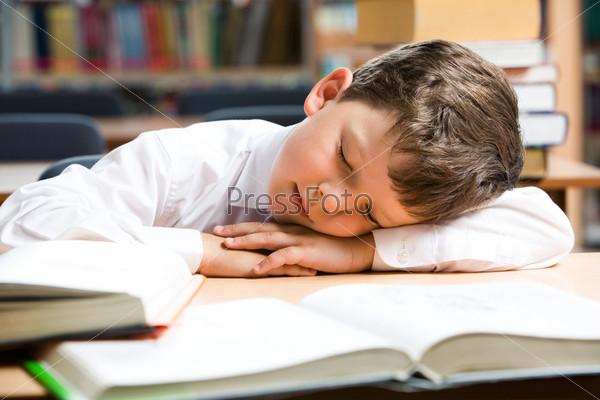 Уставший ученик спит за столом на раскрытых учебниках