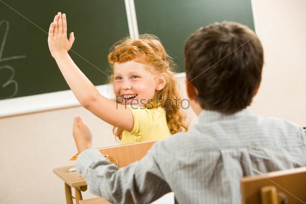 Счастливая ученица поднимает руку сидя на уроке