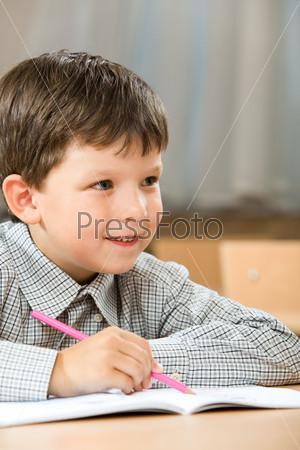 Умный мальчик сидит за столом держа в руках ручку