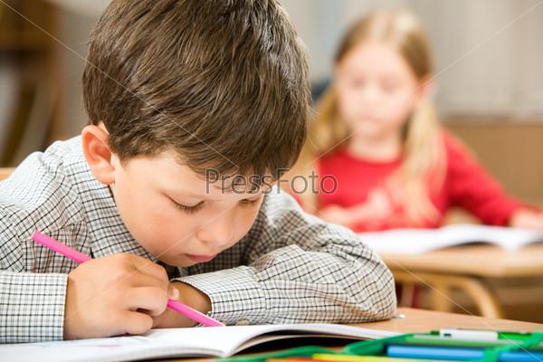 Ученик начальной школы с усердием и старанием читает книгу за партой