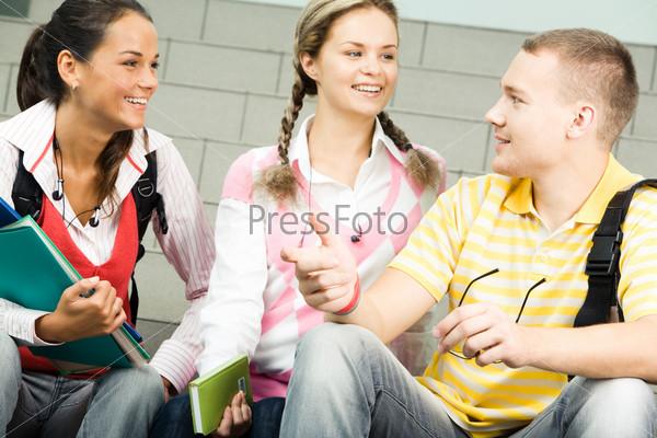 Студенты сидят и смеются обсуждая занятие глядя друг на друга