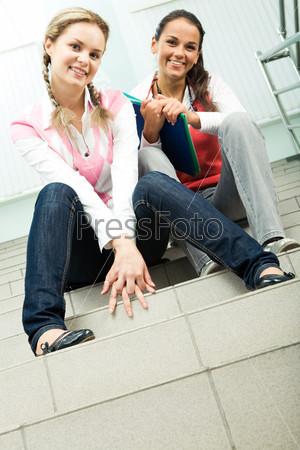 Две студентки мило улыбаются сидя на ступеньках университета
