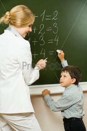 Фотография на тему Молодая учительница помогает школьнику начальных классов решить примеры на школьной доске
