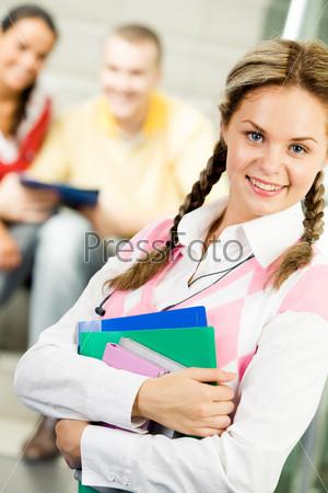Успешная студентка стоит близко к камере и улыбается на фоне своих одногруппников