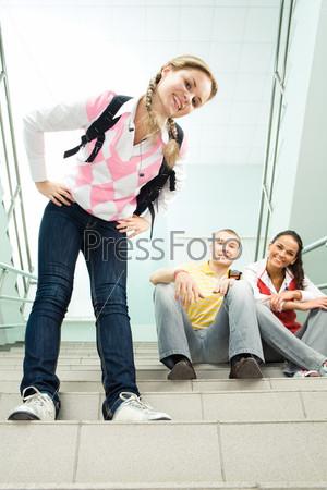 Веселая студентка улыбается в камеру, позади сидят на ступеньках лестницы ее друзья