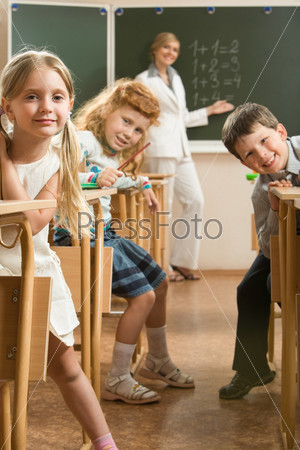 Группа школьников сидя за партами смотрит в камеру на фоне учительницы стоящей возле доски