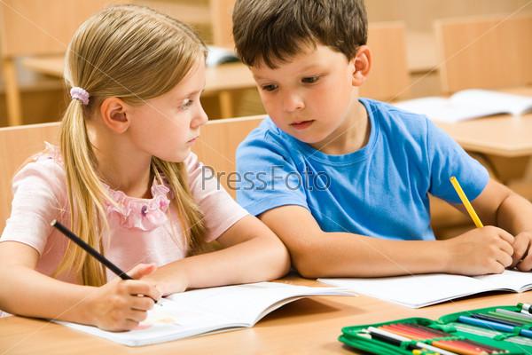 Школьник сидя за партой подсматривает в тетрадь своей соседки