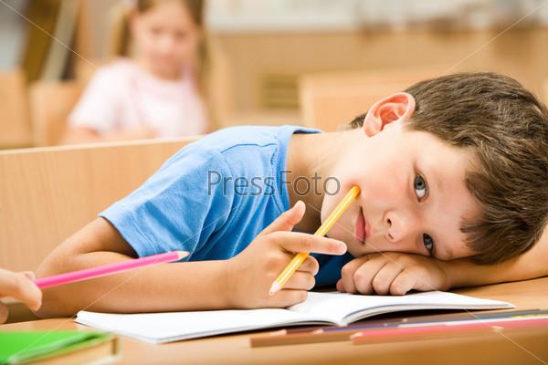 Уставший школьник лежит на парте с карандашом в руке и смотрит в камеру