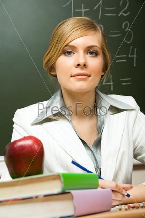 Миловидная учительница сидит за столом, перед ней стопка учебников и красное яблоко сверху