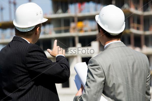 Два строителя стоя спиной обсуждают проект стройки и показывают на возводимое здание