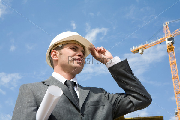 Успешный архитектор смотрит вдаль держась за козырек каски на фоне башенного крана