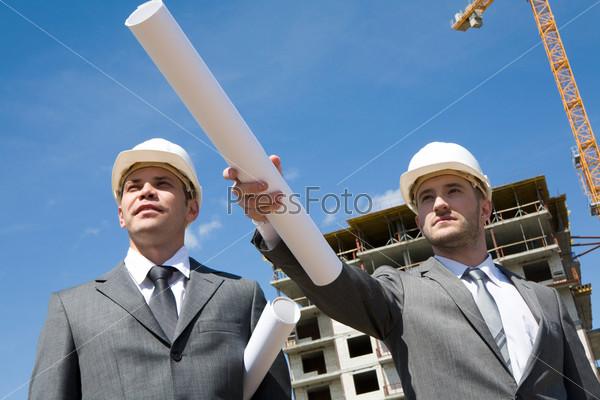 Мужчина в деловом костюме стоит на стройке вытянув руку с чертежом вперед рядом с инженером