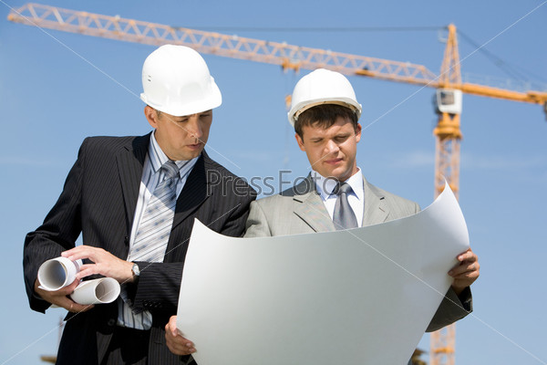 Инженер заглядывает в чертеж архитектора, который тот держит в руках на строительной площадке