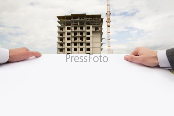 Крупный план рук строителей держащих строительный чертеж на фоне возводимого здания