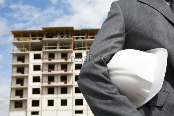 Крупный план руки в пиджаке держащей белую каску на фоне недостроенного здания