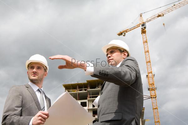 Два бизнесмена стоят на фоне строящегося здания и подъемного крана, один из мужчин показывает рукой в сторону