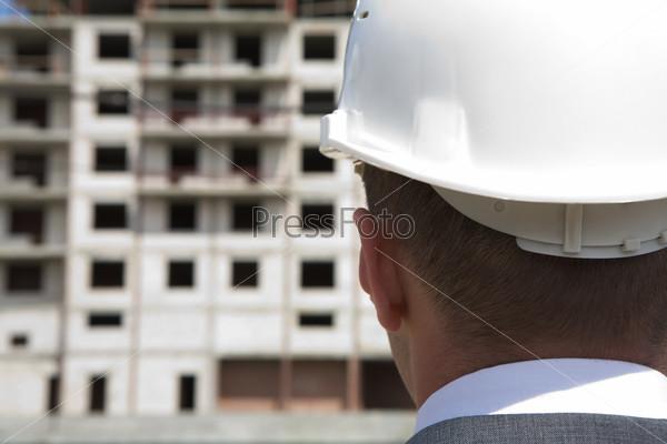 Фотография на тему Крупный план затылка строителя в каске на фоне возводимого здания