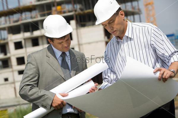 Два строителя рассматривают проект, склонившись над чертежом на фоне стройки