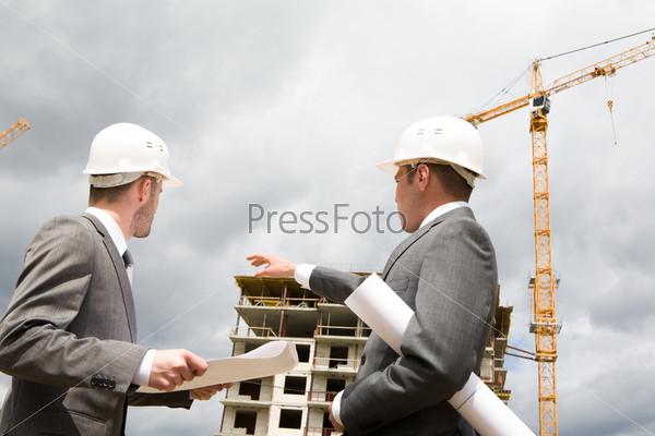 Бизнесмен показывает рукой в сторону строящегося здания инженеру, который держит в руках раскрытый плакат