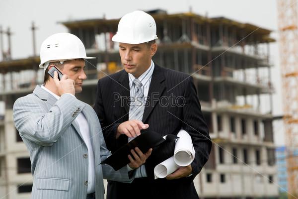 Фотография на тему Занятой начальник смотрит в раскрытую папку с документами на стройке и говорит по телефону, рядом стоит его подчиненный