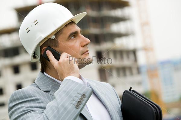 Крупный план строителя, который говорит по телефону на стройке, его взгляд устремлен вверх