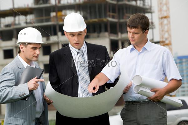 Три специалиста по строительству обсуждают  проект на площадке