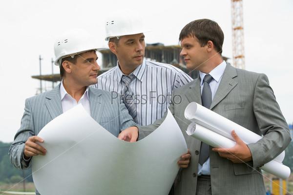 Трое строителей смотрят друг на друга, обсуждая проект возводимого здания