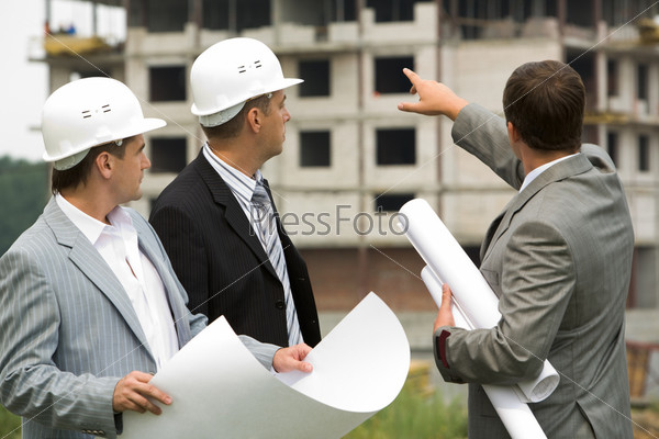 Архитектор на стройке объясняет инженерам проект будущего здания показывая рукой в сторону дома