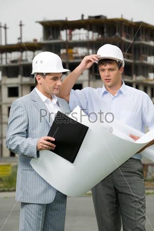 Два строителя разговаривают на площадке, раскрыв чертеж на фоне возводимого дома