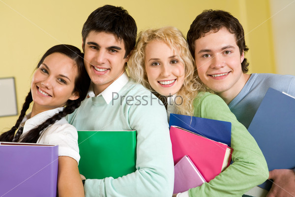 Портрет четырех счастливых студентов, стоящих рядом и объединивших свои головы и умы для совместной творческой работы.