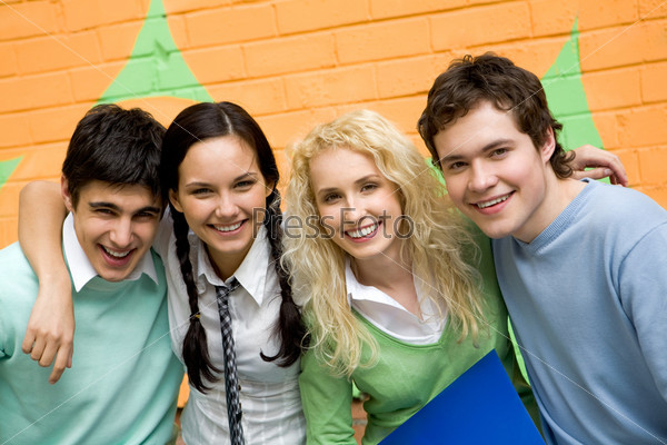 Портрет четверых улыбающихся студентов, радостно обнимающихся в знак успешной сдачи экзамена.