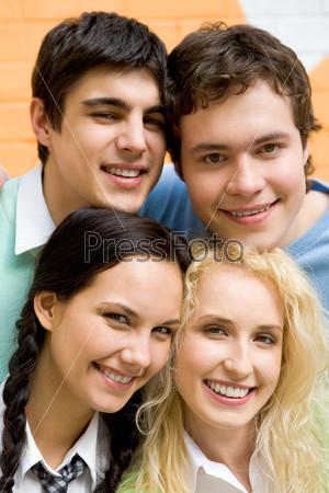 Дружная компания молодых успешных студентов смотрит в камеру и улыбается.