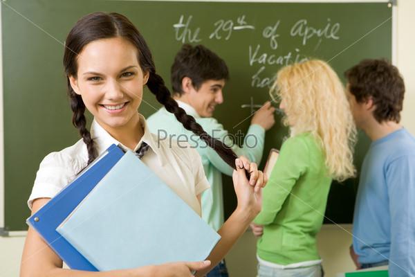 Портрет милой девушкой с учебниками в руках на фоне весело болтающих у доски студентов- одногрупников.